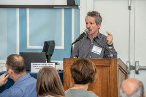 speaker at podium, hand pointing