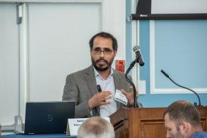 speaker at podium, gestures with hands